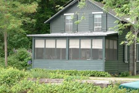 Lakefront cottage with screened-in front porch and canoes available!