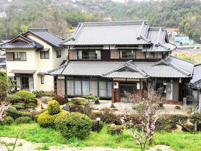桃の木に囲まれた日本家屋